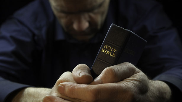 man praying with bible
