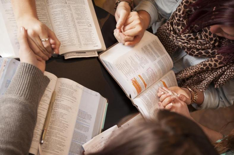 women reading bible holding hands